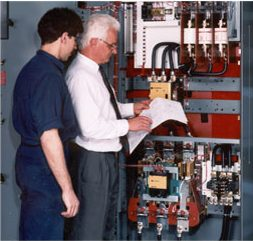 two men standing in front of electrical control system